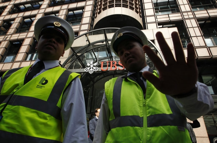 Image: A security guard gestures as he stands with a colleague in front of a UBS bank in the City of London