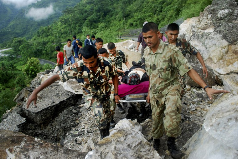 Image: Members of the Nepalese army carry an injured man at an area near a landslide after a 6.9 magnitude earthquake hit Nepal, in Dhankuta District