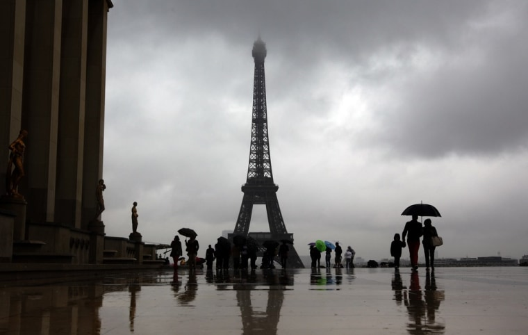 Image: Tourists protect themselves from the rain under umbrellas in front of the Eiffel tower in Paris as they visit the French capital during summer holidays