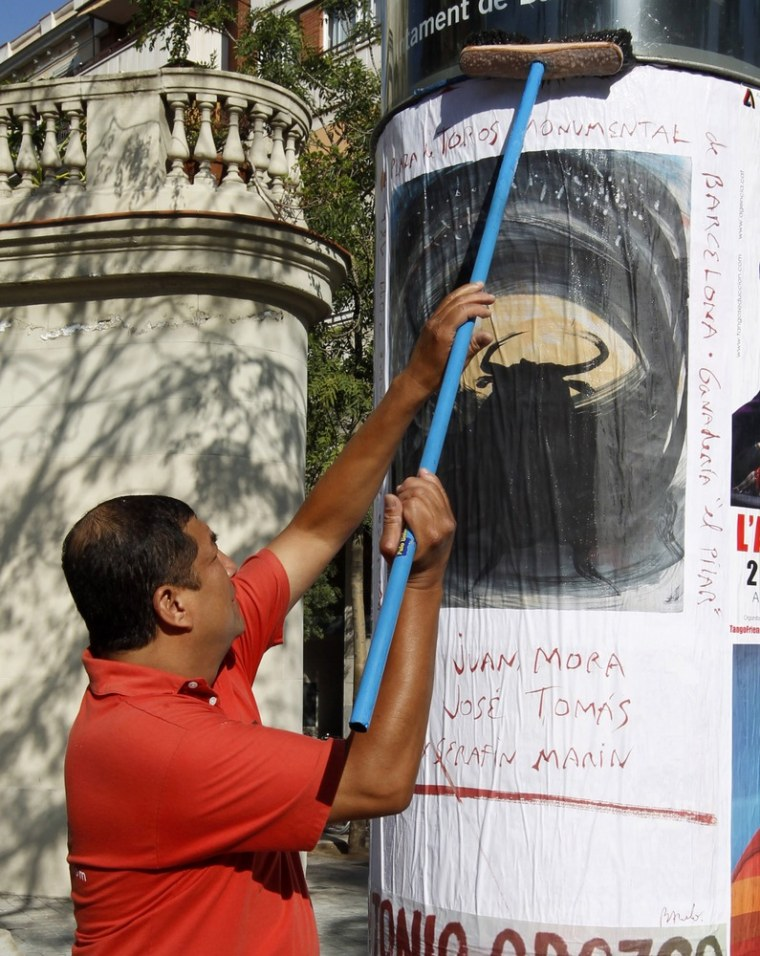Image: A worker puts up a poster by Balearic artist Barcelo, painted for his bullfighter friend Tomas to mark the last bullfight in Catalonia, in Barcelona