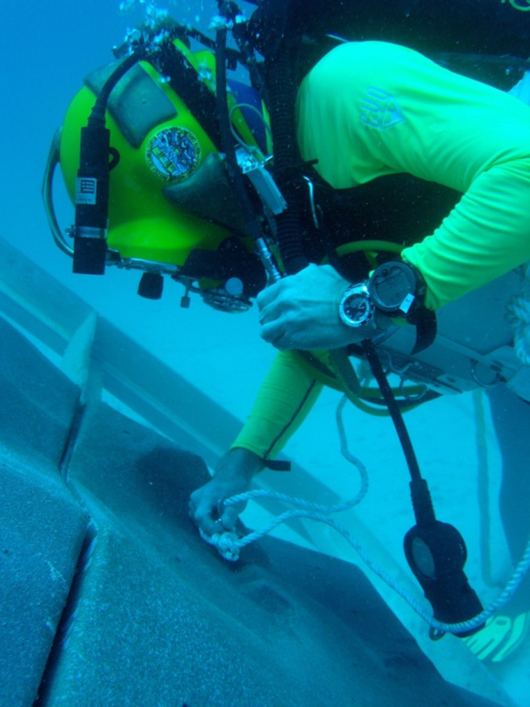 A diver anchors to a simulated asteroid surface created for NASA's underwater NEEMO 15 mission.