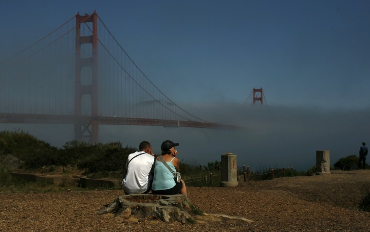 Image: A couple looks out at the fog-shrouded Golden Gate Bridge in San Francisco