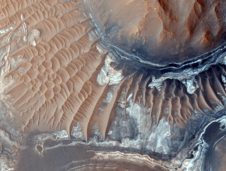 Exposed layers are seen in the Martian trench system, Noctis Labyrinthus, which may contain water-bearing deposits of clay minerals and could have once been host to life.