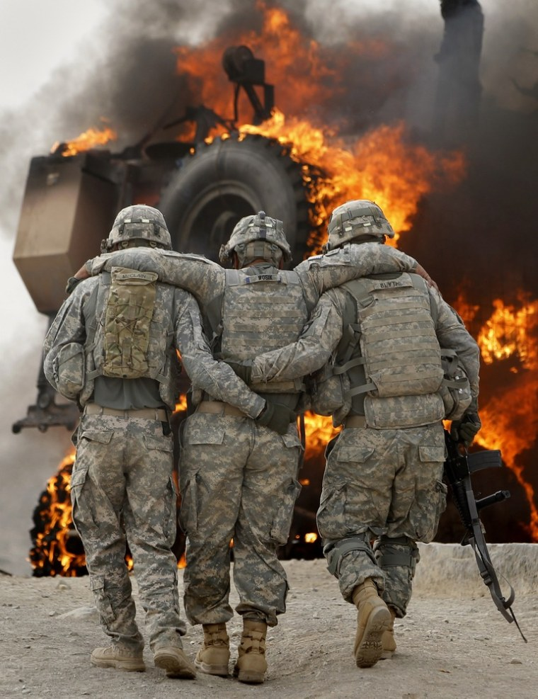 Image: A soldier with an injured ankle from the US Army's 1-320 Field Artillery Regiment, 101st Airborne Division is assisted past his burning M-ATV armored vehicle after it struck an Improvised Explosive Device (IED) in Afghanistan