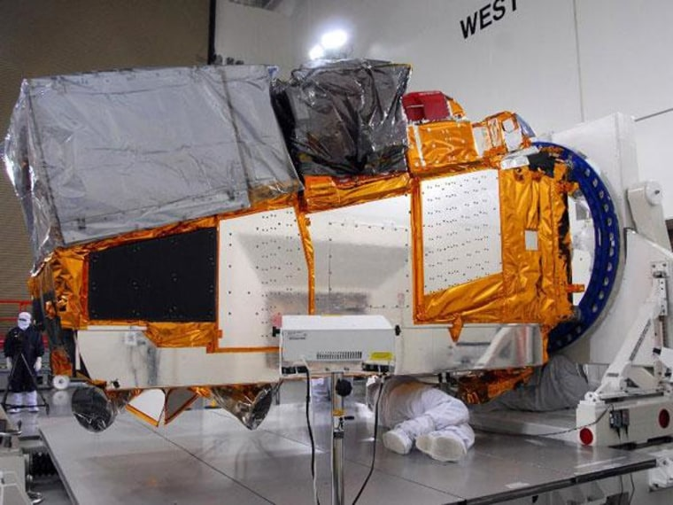 In a clean room inside the Astrotech Payload Processing Facility at Vandenberg Air Force Base in California, technicians position NASA's National Polar-orbiting Operational Environmental Satellite System Preparatory Project spacecraft for testing.