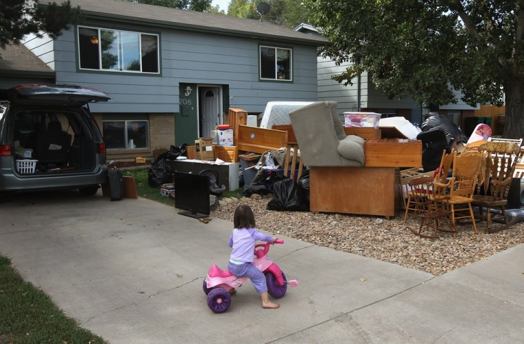Image: Caitlin Barbiere, 2 1/2, plays in the driveway as her family's possessions sit piled in the front yard during a home foreclosure eviction on October 5, 2011 in Miliken, Colorado