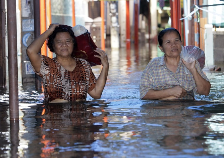 Image: Thai villagers with their belongings wade through floodwaters in Pak Kred district in Nonthaburi province, Thailand