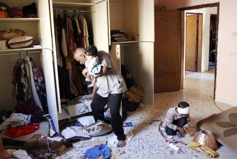 Image: Residents look through their belongings in their home in the Libyan city of Sirte