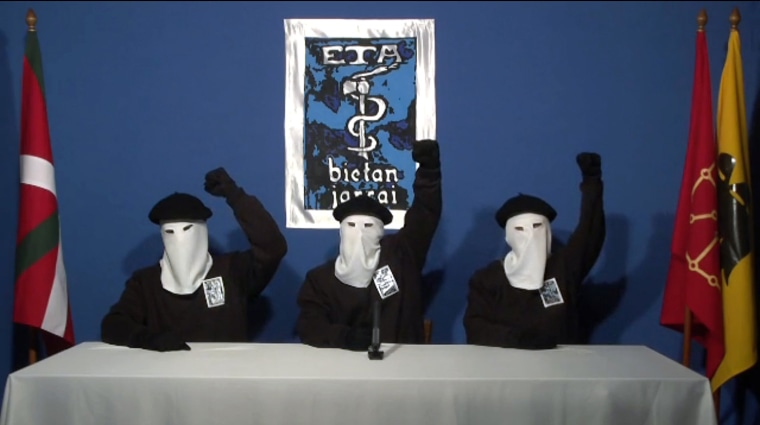 Image: hree ETA militants dressed in black shirts with white hoods over the heads