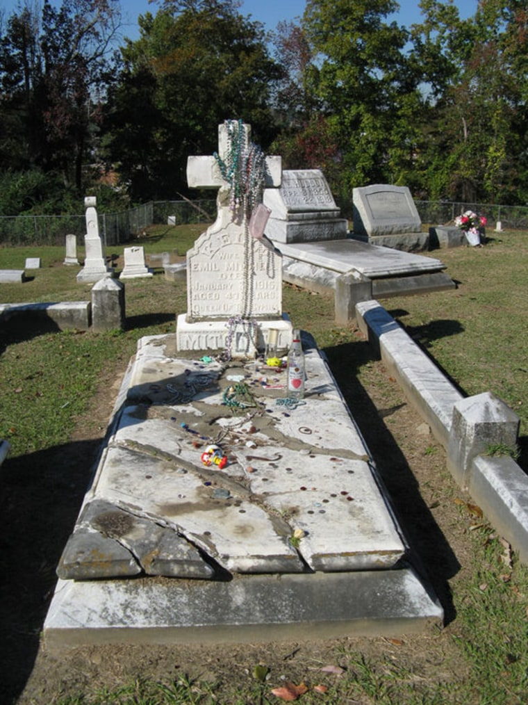 The grave of the gypsy queen Kelly Mitchell, where her visitors leave gifts. Botanists think her followers may also have introduced a foreign plant, called blue sedge, to Mississippi.