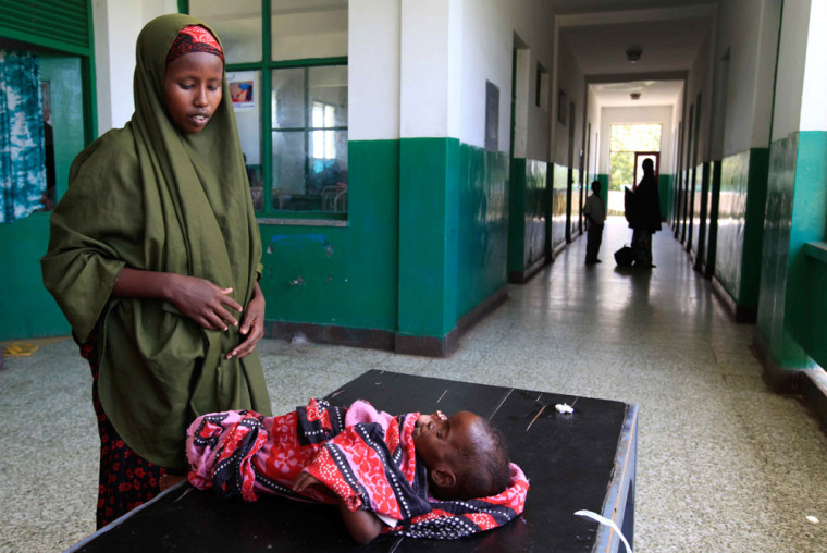 Image: Somali woman attends to her malnourished child along corridor of paediatric ward at Banadir hospital in southern Mogadishu