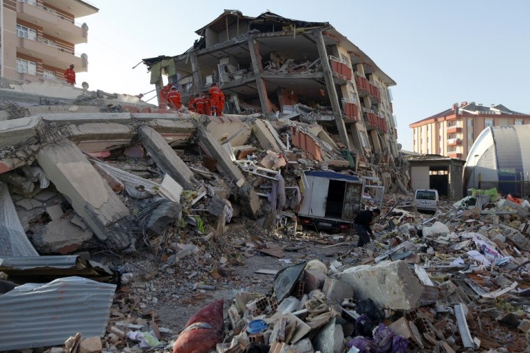 Image: Rescue workers work to save people trapped under debris after an earthquake in Ercis