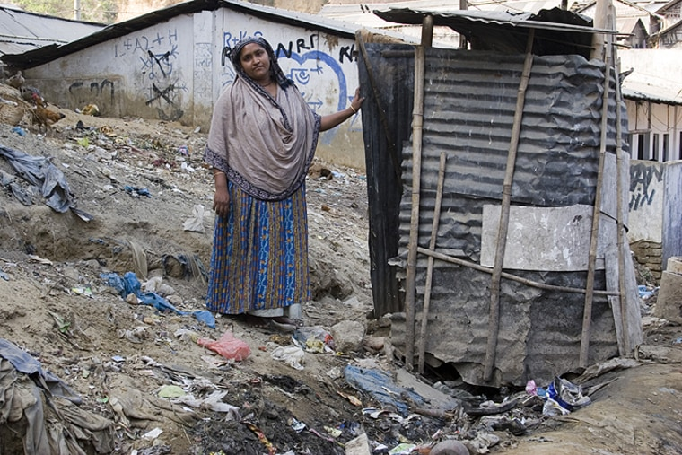 A woman stands beside a makeshift latrine inDhaka, Bangladesh. More than 200 million tons of human waste goes untreated every year.