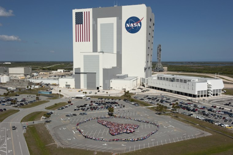 Thousands of NASA Kennedy Space Center employees stand side-by-side to form a full-scale outline of a space shuttle orbiter outside the Vehicle Assembly Building on March 18. The photo was designed to honor the space shuttle program's 30-year legacy.