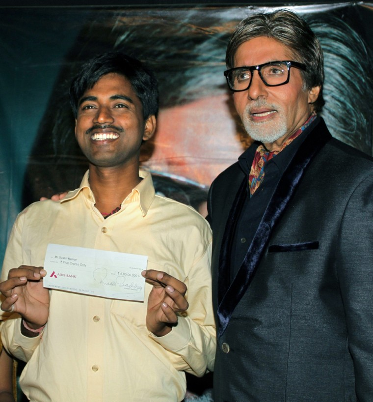 """Sushil Kumar, left, with Bollywood actor Amitabh Bachchan, shows his $1 million check after his appearance on the popular Indian version of """"Who wants to be a Millionaire."""""""