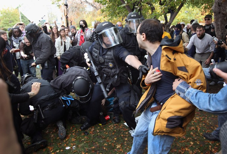 Image: Policemen in riot gear scuffle with protesters