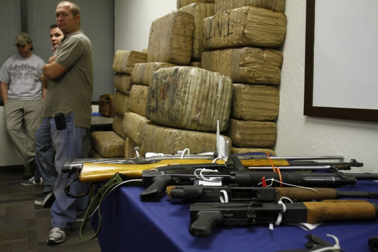 """Image: Guns and bundles of marijuana seized from the Mexican Sinaloa Cartel during \""""Operation Pipeline Express\"""" are displayed at a news conference in Phoenix"""