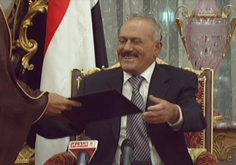 Image: Yemeni President Ali Abdullah Saleh smiling as he signs a Gulf Cooperation Council-sponsored transition deal to exit power