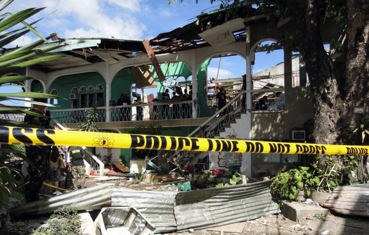 Image: Investigators sift through rubble inside a destroyed hotel in Zamboanga City, in the Philippines southern island of Mindanao