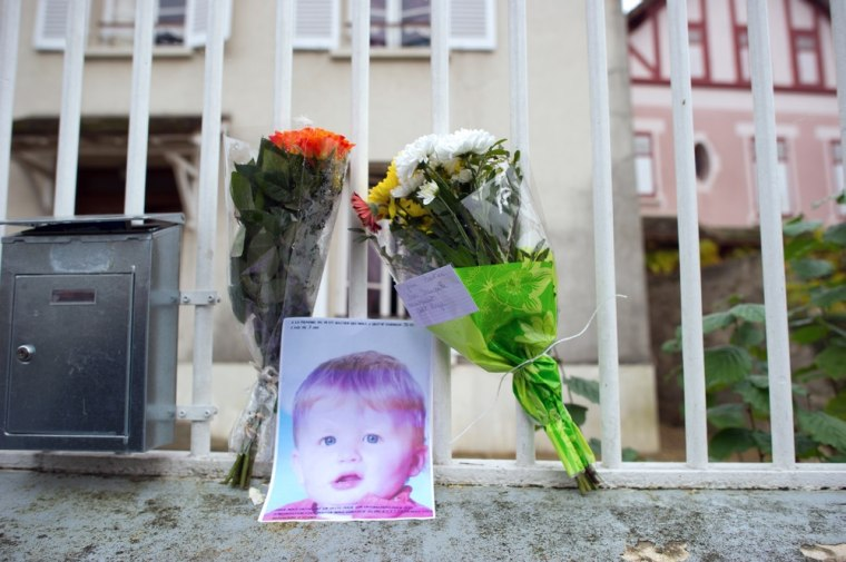 Image: Flowers and a picture of three-year-old child Bastien are seen at the entrance of the child's parents house.
