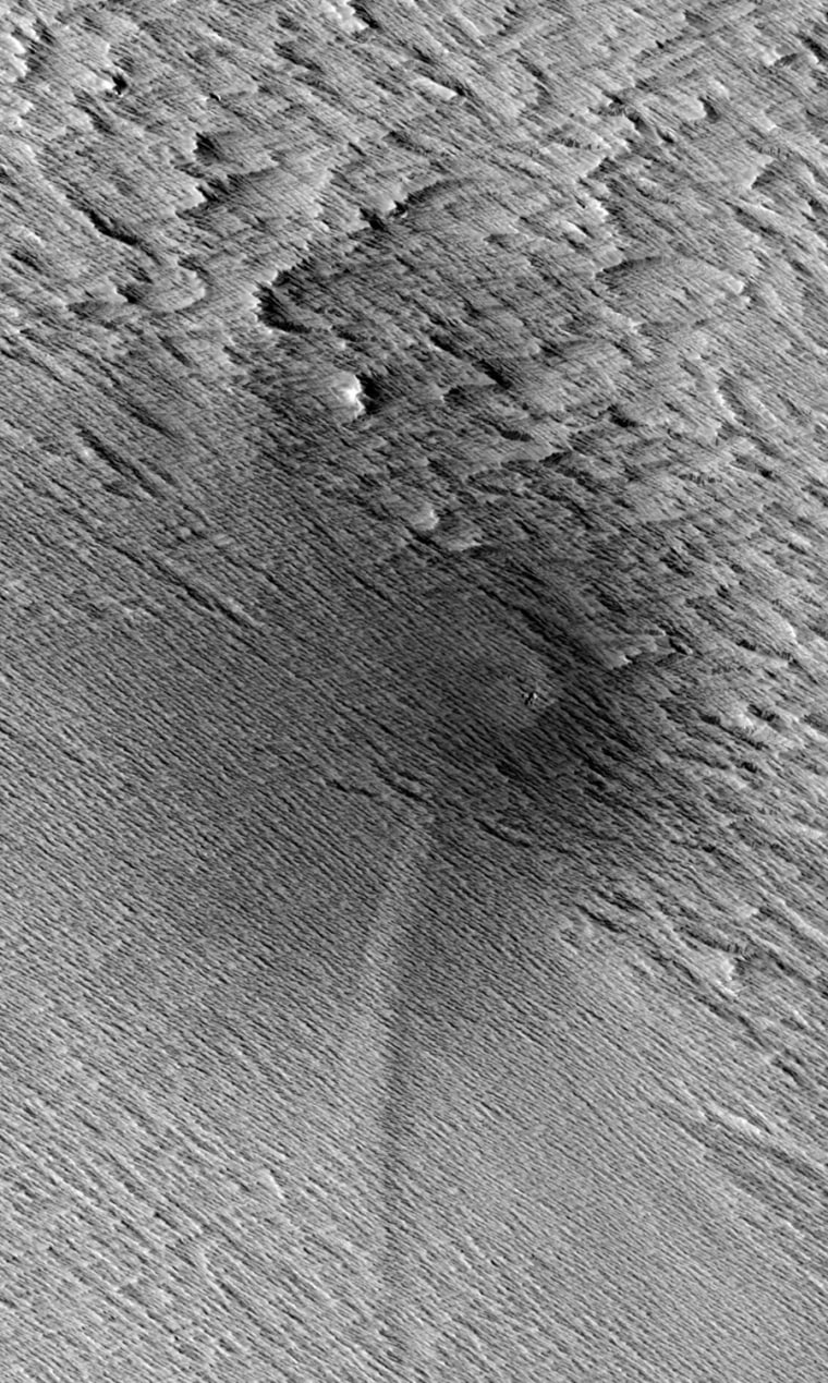 This HiRISE image from NASA's Mars Reconnaissance Orbiter shows a central crater on Mars with two dagger-like features extending at an angle. Called scimitars, these features most likely resulted from shockwave interference just before impact, scientists say.