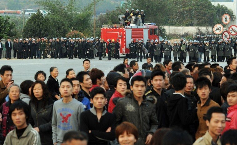 Image: Police block villagers after a large crowd formed at the scene of environmental protests over the past few days in the town of Haimen, Guangdong Province