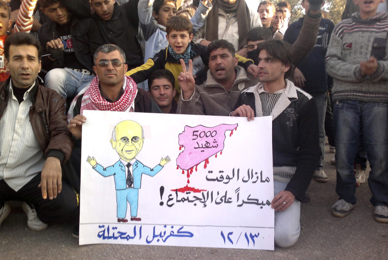 Image: Demonstrators against Syria's President al-Assad hold a poster with a picture representing Arab League Secretary General Elaraby in Kafranbel near Adlb