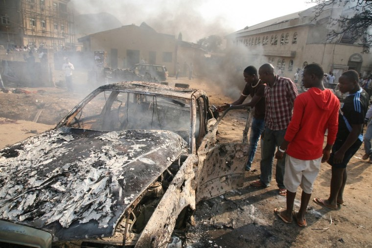 Image:Men look at the wreckage of a car following a bomb blast