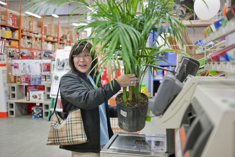 Anne Hidaka looks for help from a cashier while attempting to scan her potted palm plant in the automated self-checkout lane at a Home Depot in Seattle. The bar code placement on tall pots can be difficult to scan, causing people to tip the plants and spill soil.