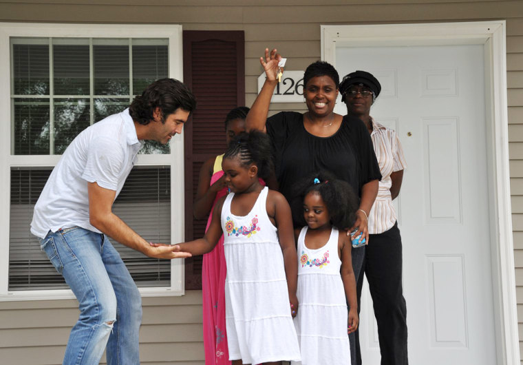 Carter Oosterhouse slaps fives moments after he hands over the keys to the Dunmore family's new home.