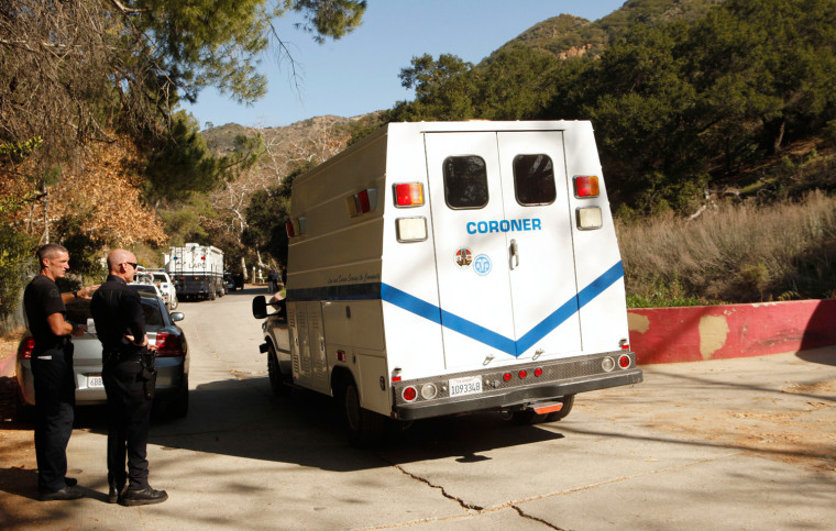 Image: A Los Angeles County Coroner vehicle and Los Angeles police officers are seen in Bronson Canyon