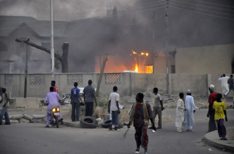 Image: People watch as smoke rises from the police headquarters after it was hit by a blast in Nigeria's northern city of Kano