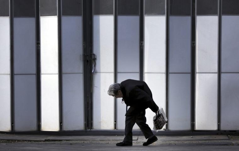 Image: An elderly woman walks in Tokyo