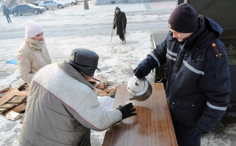 Image: A social employee gives out a hot meal and hot tea to an elderly man at one of newly opened shelters in the western Ukrainian city of Lviv