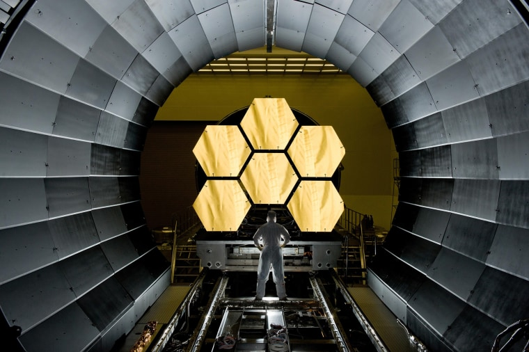 NASA engineer Ernie Wright looks on as the first six flight-ready James Webb Space Telescope's primary mirror segments are prepped for final cryogenic testing at NASA's Marshall Space Flight Center.