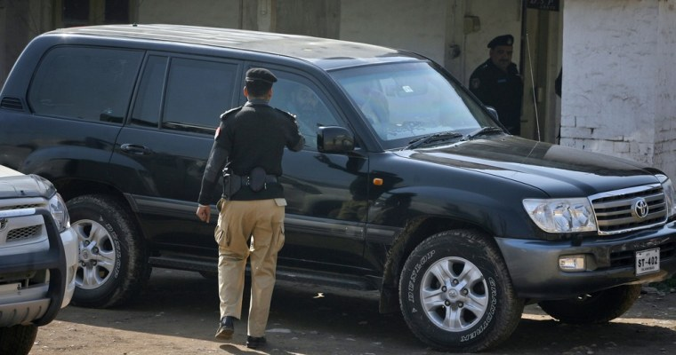 Image: A policeman gestures towards the vehicle of an American national who was held for questioning at a police station in Peshawar