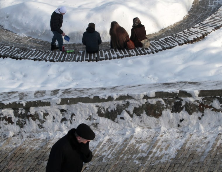 Image: People spend time in a snow-covered park in Kiev