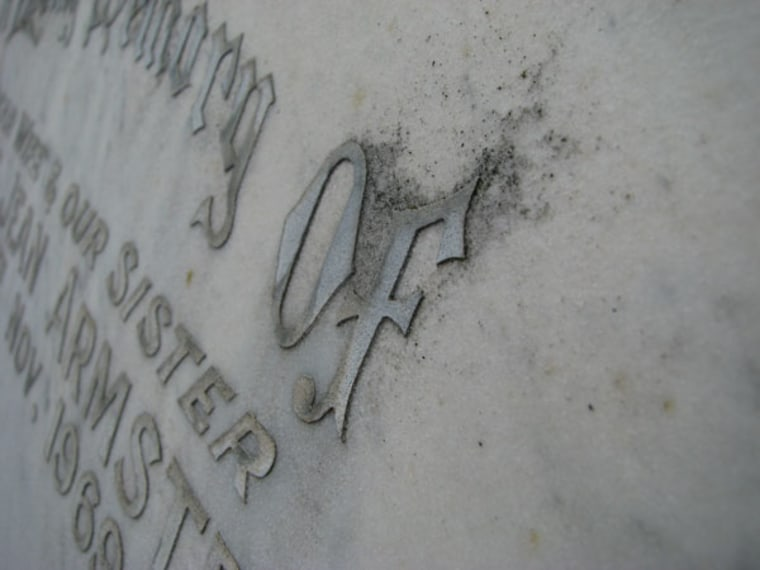 Lead lettering on a gravestone in Sydney, Australia. Volunteers measure the distance between the lettering and the stone to show how much the stone has weathered since it was put into the ground.