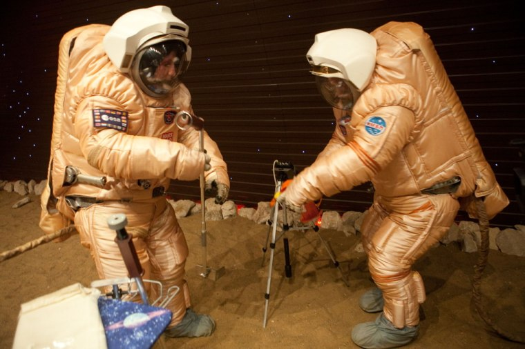"Crew training for ""Marswalk"" at the simulated Martian terrain of the Mars500 experiment. The terrain was covered with reddish sand and built to resemble the surface at Gusev crater. On the ""surface,"" they conducted simulated scientific research by driving a rover and working with sensors to gather measurements."