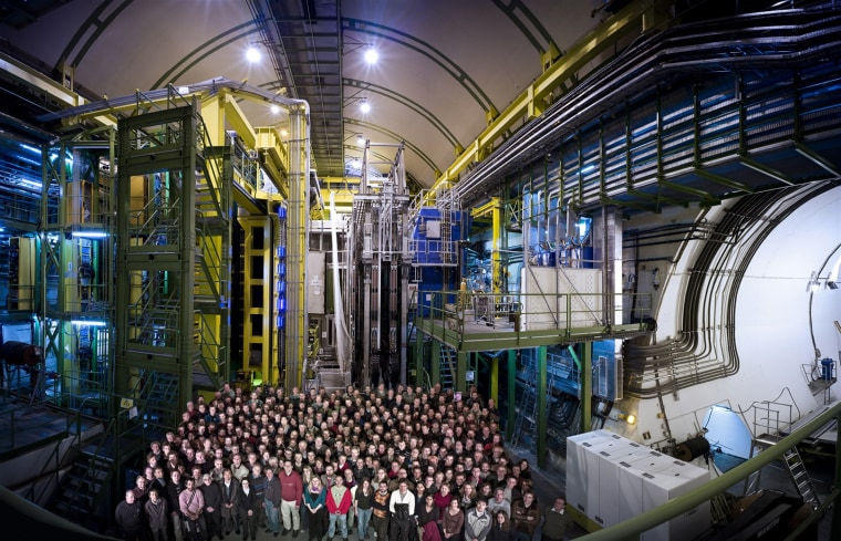 Members of the LHCb team stand in front of their experiment, the LHCb detecor, at the Large Hadron Collider in Geneva.