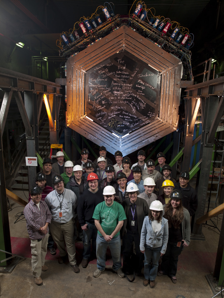 Scientists stand with the Minerva neutrino detector, located 330 feet underground at Fermi National Accelerator Laboratory.