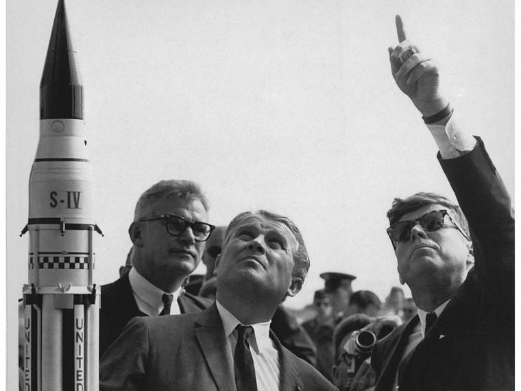 Dr. Wernher von Braun (center) describes the Saturn Launch System to President John F. Kennedy (right, pointing). NASA Deputy Administrator Robert Seamans stands to the left of von Braun.