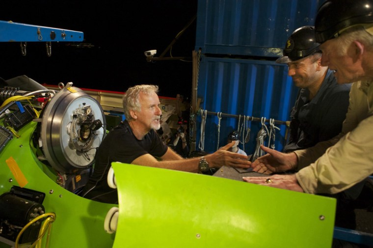 Filmmaker and National Geographic explorer-in-residence James Cameron gets a handshake from ocean explorer and U.S. Navy Capt. Don Walsh, right, just before the hatch on the Deepsea Challenger submersible is closed and the voyage to the deepest part of the ocean begins.