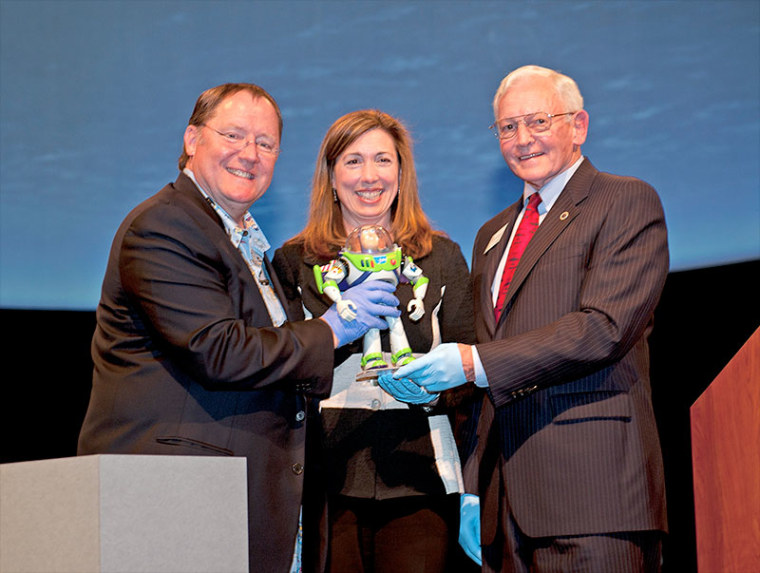 John Lasseter, chief creative officer at Pixar Animation Studios and creator of Buzz Lightyear; Lori Garver, NASA deputy administrator and National Air and Space Museum Director Jack Dailey hold the space-flown Buzz Lightyear action figure.