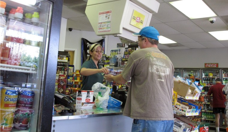 Image: Store clerk Sierra Allison completes a transaction with a customer at the Lake Wylie Minimart in Lake Wylie, S.C