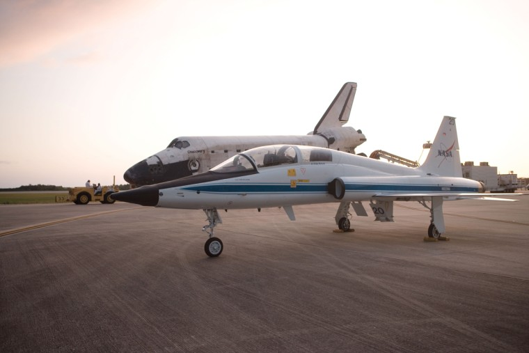 Two NASA T-38 jets, like the one seen here in the foreground, will scout the skies ahead of space shuttle Discovery (background) arriving in Washington, D.C.