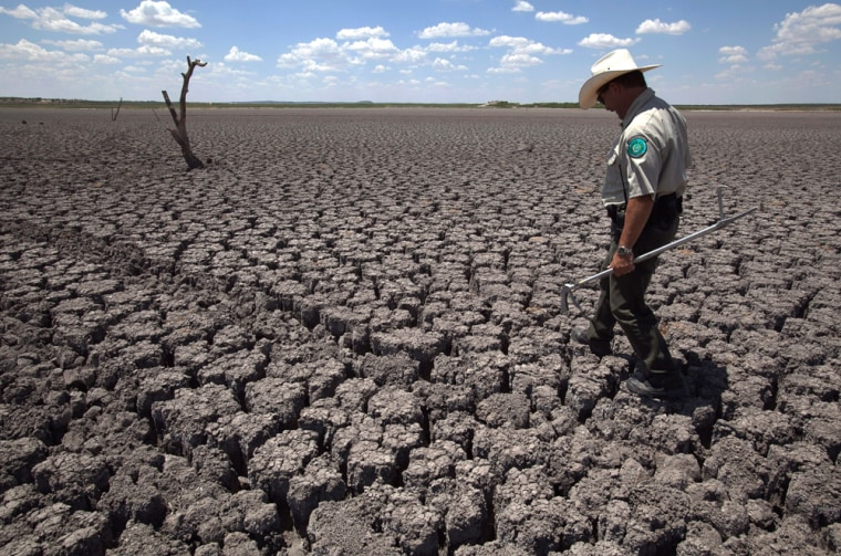 Image: Texas State Park police officer Thomas Bigham walks across the cracked lake bed of O.C. Fisher Lake