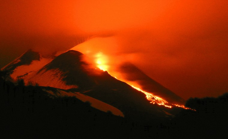 Italy's Mount Etna glows as lava pours down its flanks.