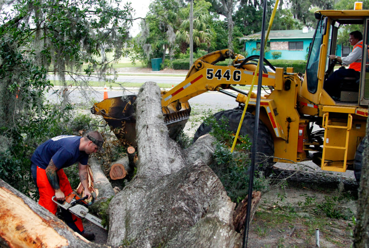 Image: A crew from the Florida Department of Transportation works to clean up the debris of a tree that fell and damaged the home of Geneva Sercey in Gainesville, Fla., in the aftermath of Tropical Storm Beryl on Monday.