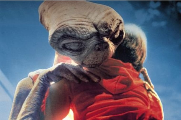 """A still photo of ET hugging Henry Thomas in the 1982 film """"ET: The Extra-Terrestrial."""""""